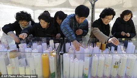 Phụ huynh thắp nến cầu nguyện cho con em mình tại một ngôi đền ở Seoul
