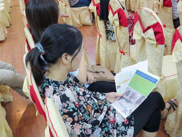 Một phụ huynh chăm chú xem tài liệu về trường